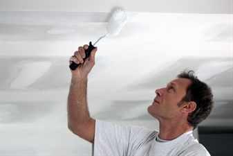 мужчина красит потолок