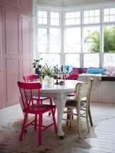 Круглый белый стол с розовыми и белыми стульями