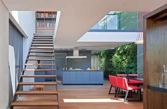 Комната с голубой кухней и красным столом
